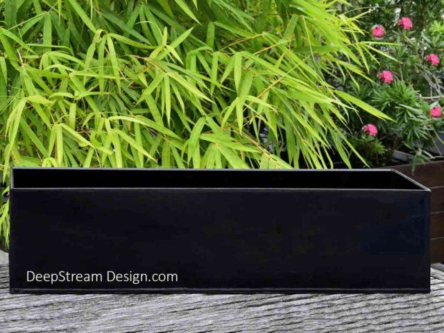 A Custom Welded Waterproof Plastic Planter Liner shown on a table in front of bamboo in a tropical roof deck garden