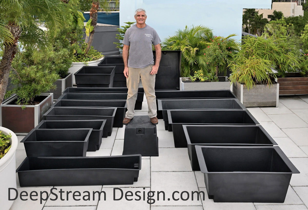 16 sizes of DeepStream's waterproof planter liners on a tropical penthouse roof deck with a man standing on top of one to show their strength.