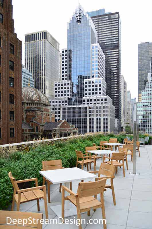 A long, lushly landscaped, multi-section Restaurant Planter forms a parapet wall behind a long row of outdoor dining tables on a midtown Manhattan roof deck with NYC skyscrapers as a dramatic urban backdrop.
