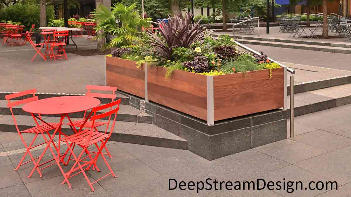 Large rectangular wood Restaurant Planters filled with flowering plants separate dining spaces with bright orange chairs and tables on a granite city center plaza, and act as parapet walls around steps between levels.