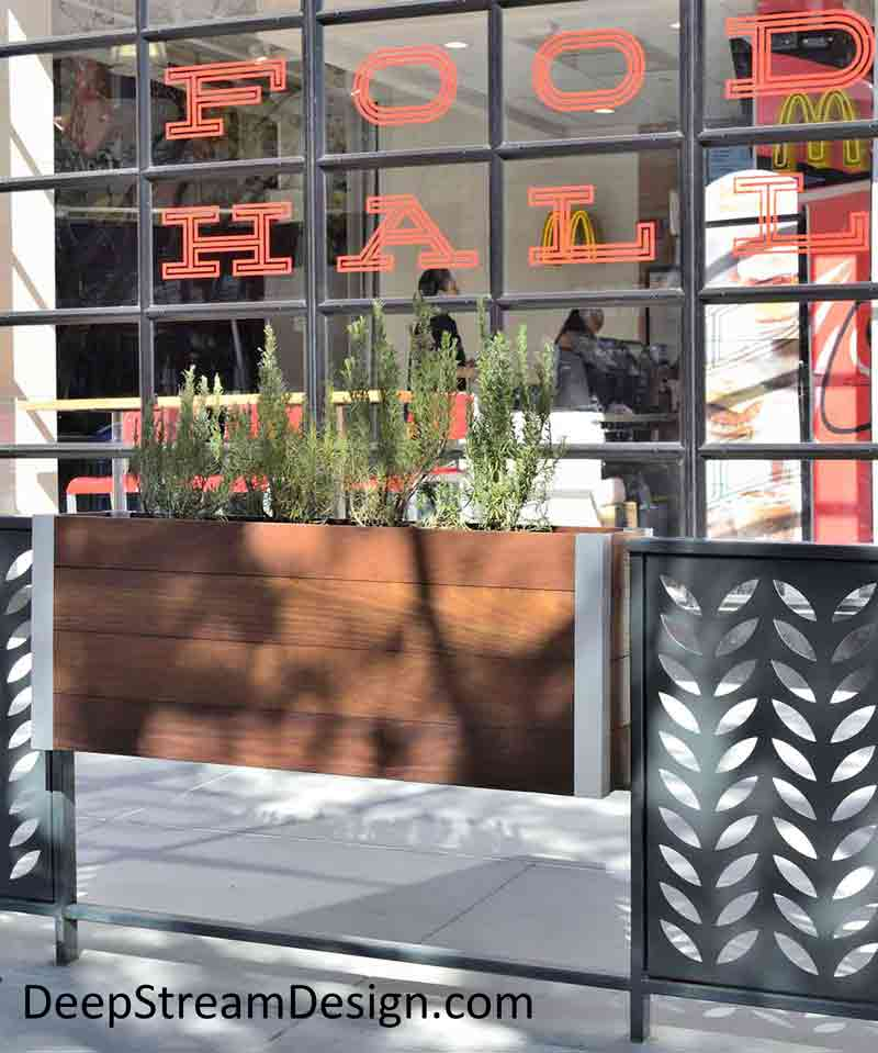A landscaped railing-mounted Modern Mariner wood and aluminum Planter adds a touch of nature to the outdoor sidewalk seating area of an urban Food Hall.