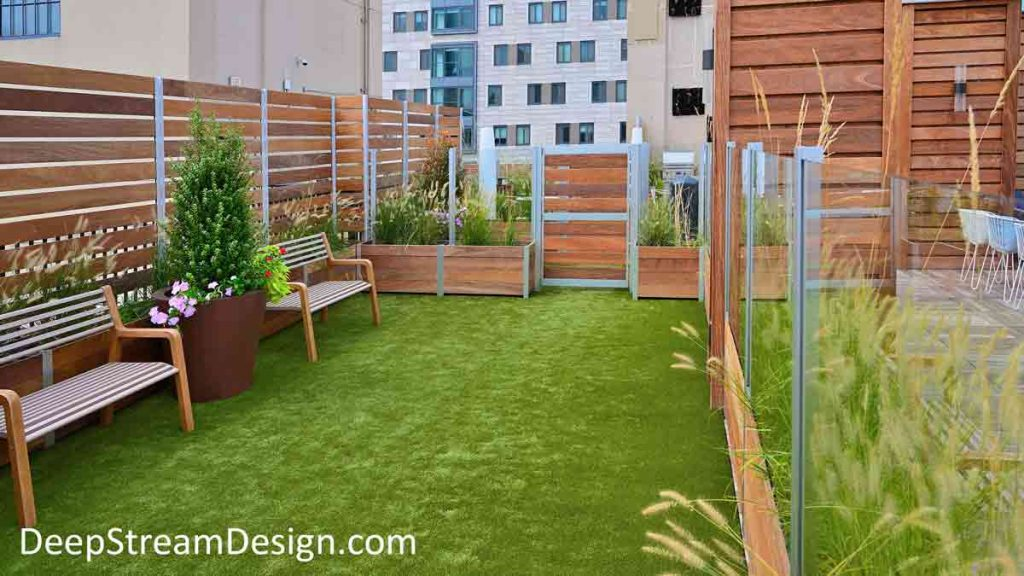 An urban roof deck equipped with landscaped Mariner Planters anchoring wood and glass screen wall to create a convenient urban dog park for tenants.