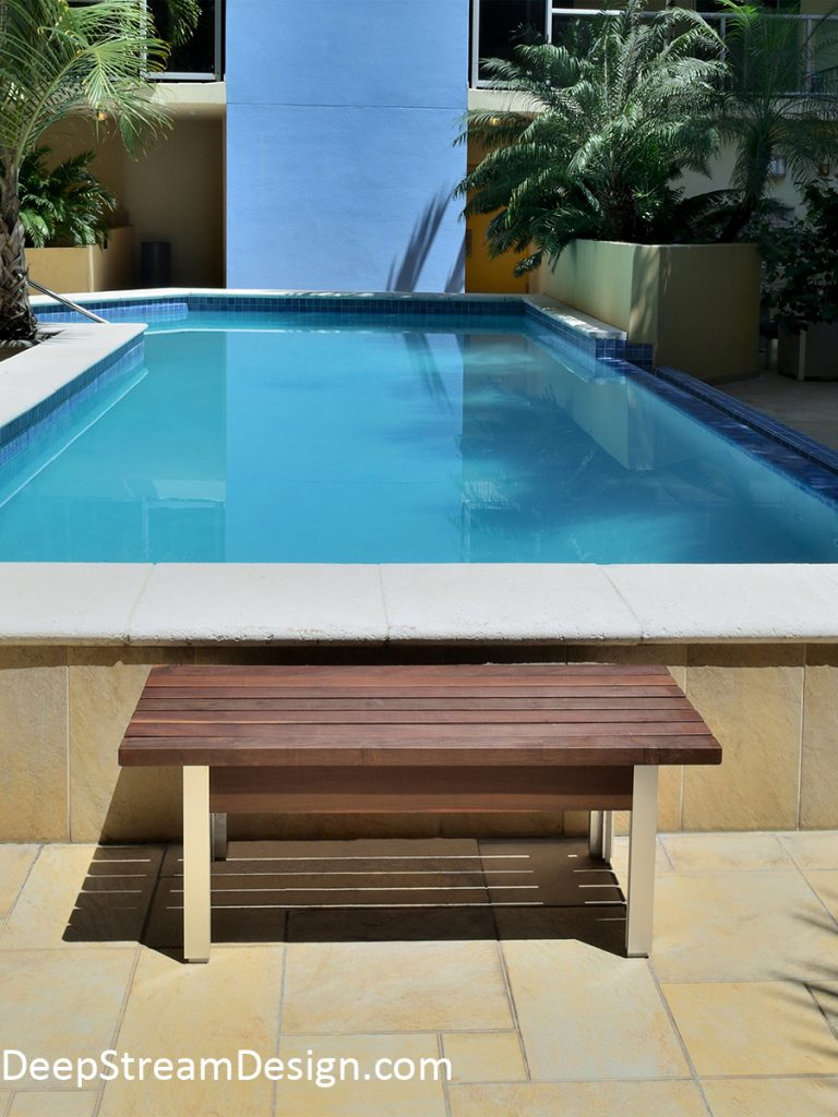 A modern outdoor Ipe gallery bench provides a comfortable seat set against the modern backdrop of a turquoise blue pool and light blue wall of a modern Miami condo courtyard green with tropical palms.