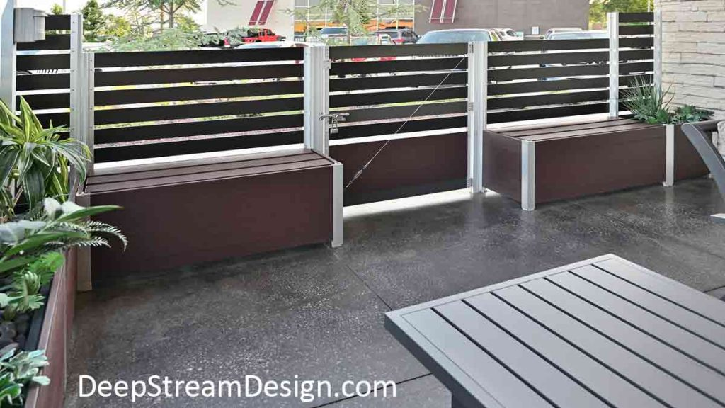 The interior view of a restaurant's outdoor smoking section on the sidewalk adjacent to the parking lot created using maintenance free Ipe Brown recycled plastic lumber Restaurant Planters with integrated bronze anodized aluminum screen wall, gate, and storage benches.