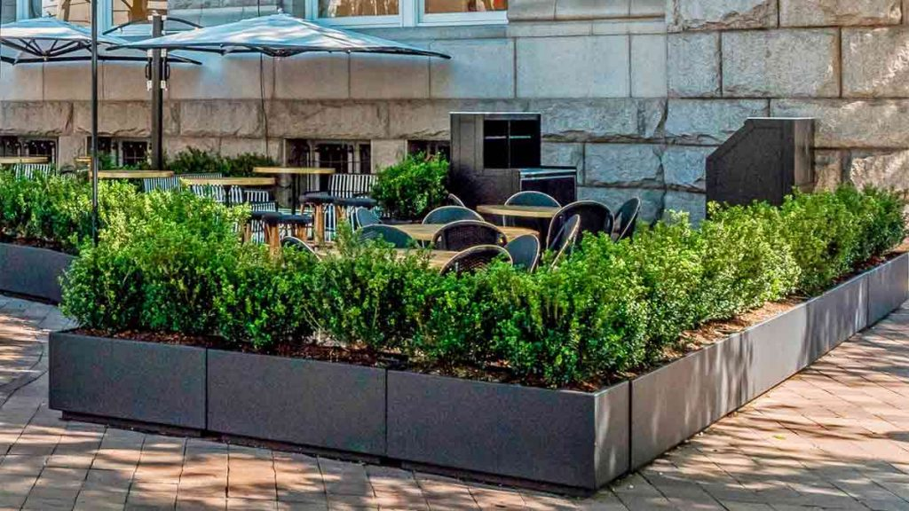 12 bronze painted aluminum restaurant planters landscaped with bushes create an outdoor dining area for a restaurant next to a historic stone building.