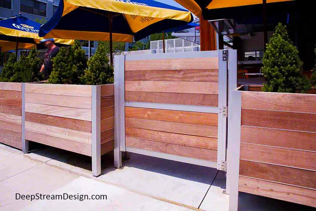 Modern wood and aluminum commercial Mariner Planters landscaped with bushes support a garden gate controlling access to a restaurant's outdoor seating area, fitted out with bright yellow and blue umbrellas for shade.