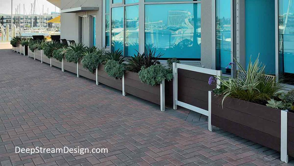 Modern, no-maintenance recycled plastic lumber and anodized aluminum commercial Mariner Planters, landscaped with bushes, flowers, and ornamental grass support garden gates controlling access to the private outdoor seating areas of modern condo units at ground level facing a public walk and marina.