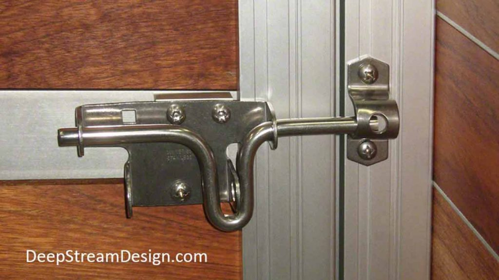 Detailed photo of a sliding, lockable, stainless-steel latch for a garden gate mounted to a wood and aluminum planter supports.