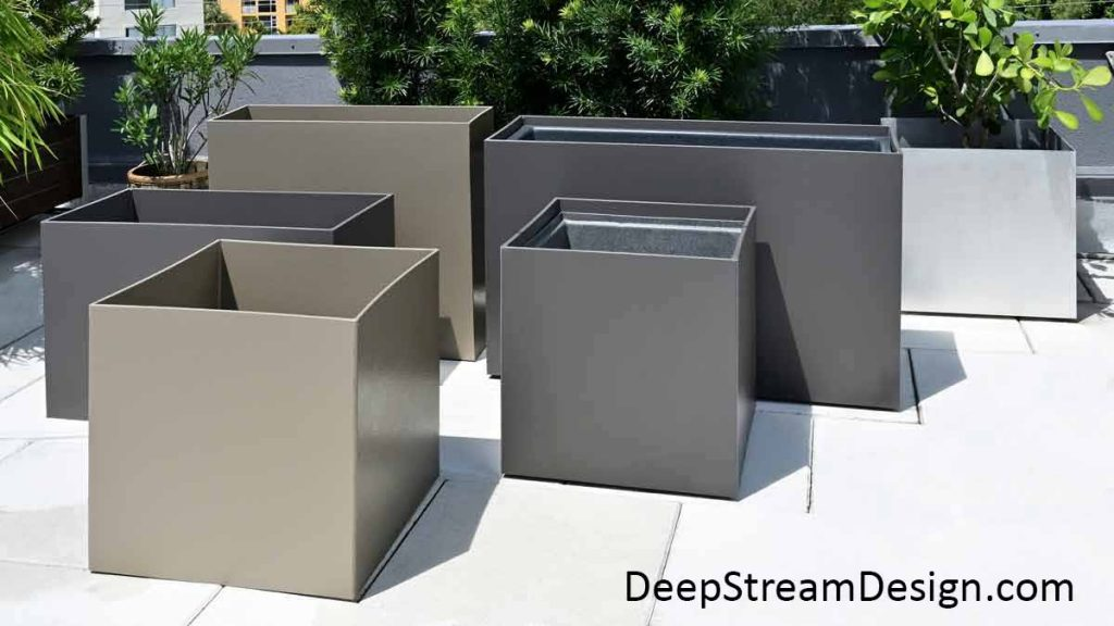 A cluster of 6 Modern Movable Commercial Plastic Restaurant Planters showing both rectangular and square forms of different heights in both Shale Gray and Hammered Nickel colors on a tropical roof deck.