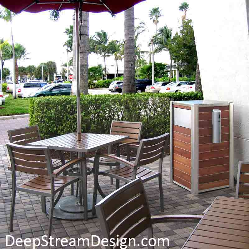 Modern Commercial Restaurant Trash Receptacle with Smokers' Outpost mounted on the side at a tropical shopping center sidewalk cafe with wood tables and chairs.