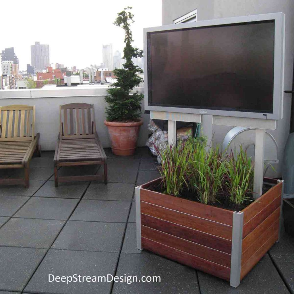 A movable commercial Mariner Wood Planter on caster wheels also holds a 65-inch outdoor TV on an urban roof deck seating area.