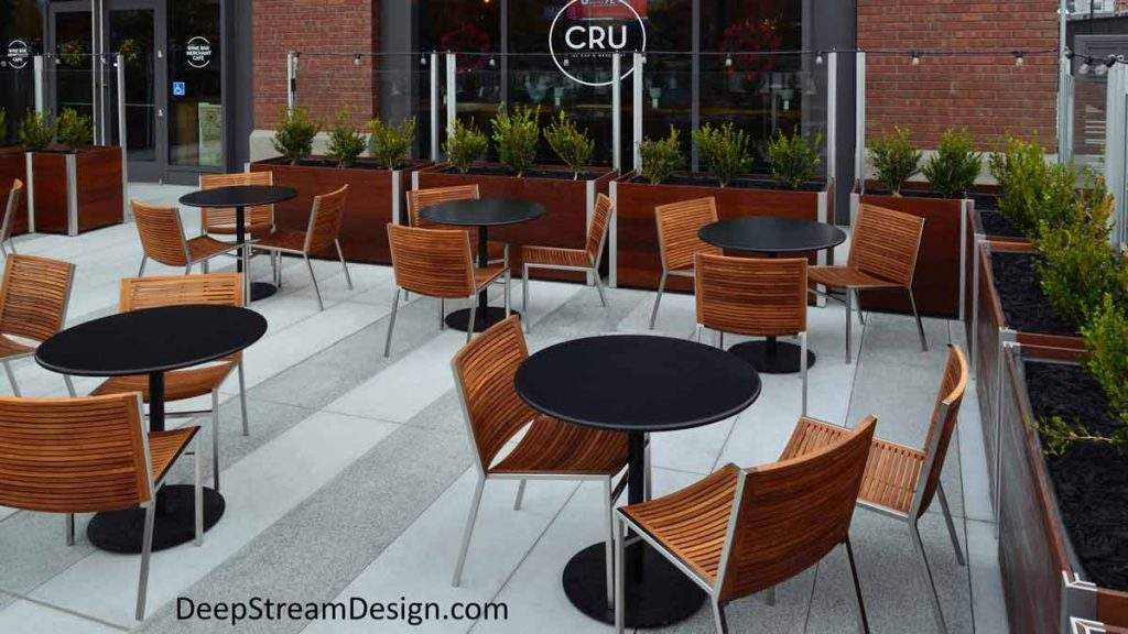 Large movable Mariner Wood Planters on wheels with glass screen wall control access, block wind and sound creating an upscale outdoor seating area with wood chairs and round tables for additional space in front of a wine themed restaurant.