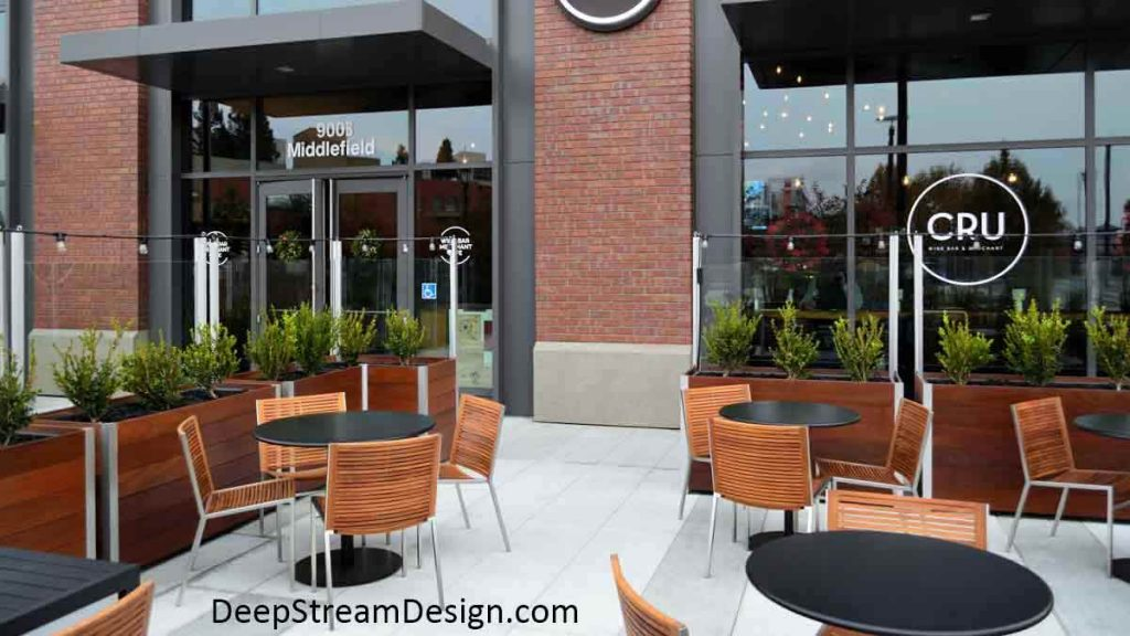 Rectangular Commercial Wood Planters, landscaped with bushes, create an upscale outdoor seating area with wood chairs and round tables in front of a brick building. The planters have a glass windbreak attached to them which is topped by small perimeter lights.