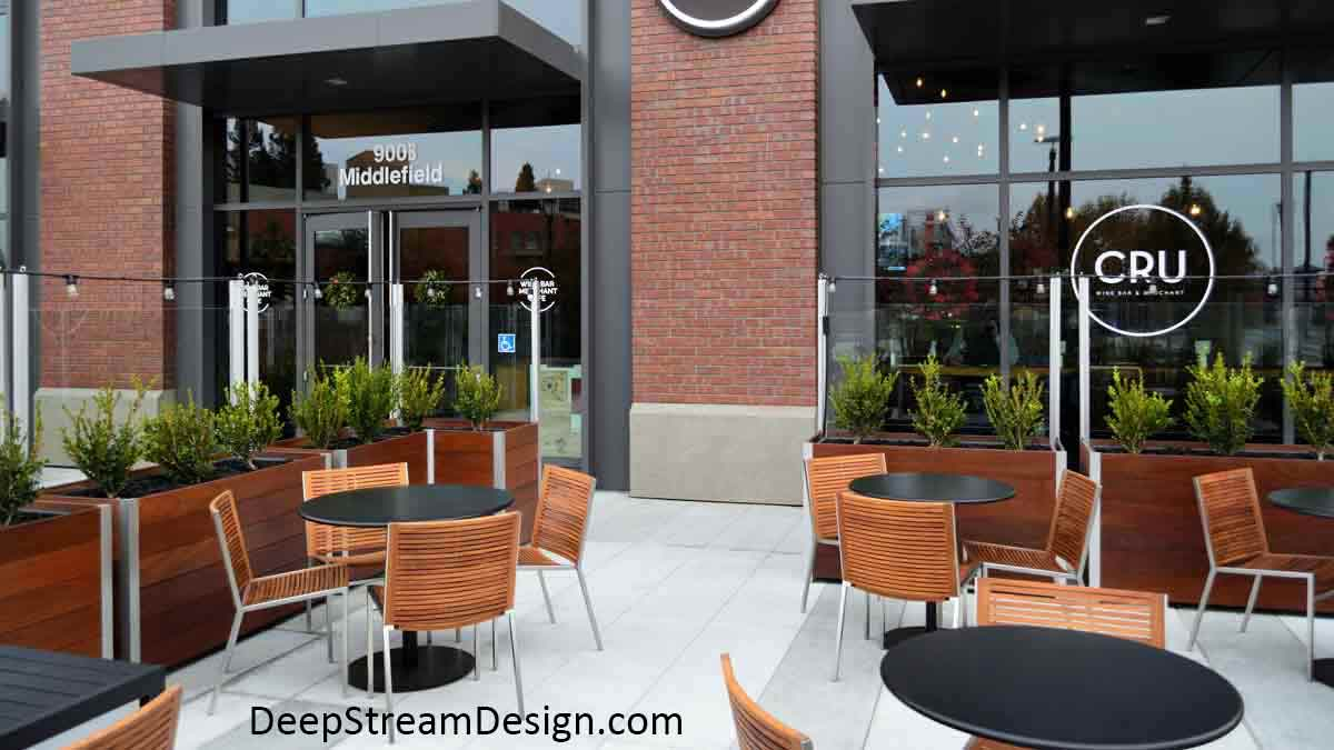 Rectangular wood Commercial Restaurant Planters, landscaped with bushes, create an upscale outdoor seating area with wood chairs and round tables in front of a brick building. The planters have a glass windbreak attached to them which is topped by small perimeter lights.