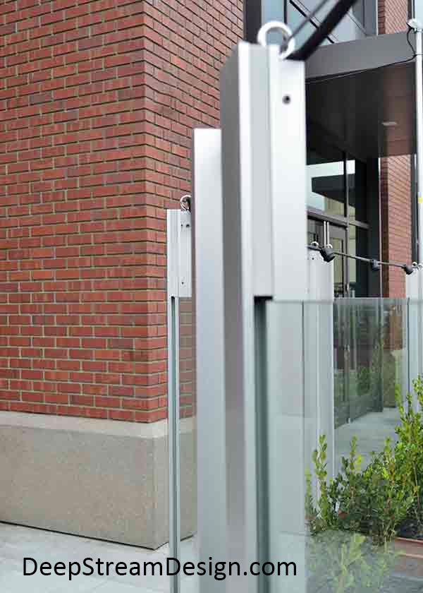 Restaurant planters landscaped with bushes hold glass windbreak screen wall panels and with a string of lights on top.