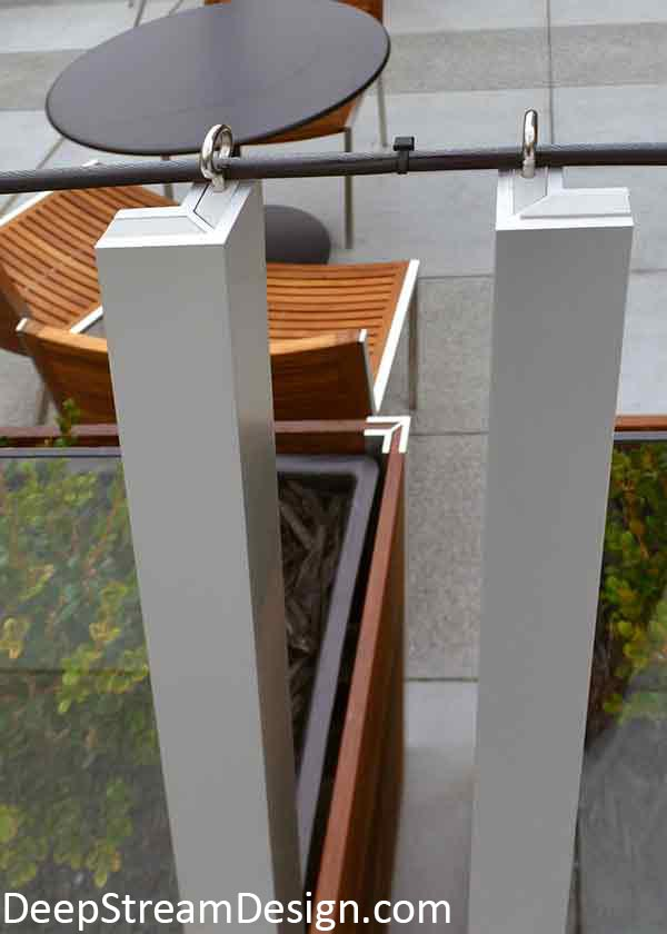 Restaurant planters create an outdoor dining area. They use a threaded eye bolts added to the top of the plastic blocks holding the glass panels in the aluminum legs to hold a string of lights.
