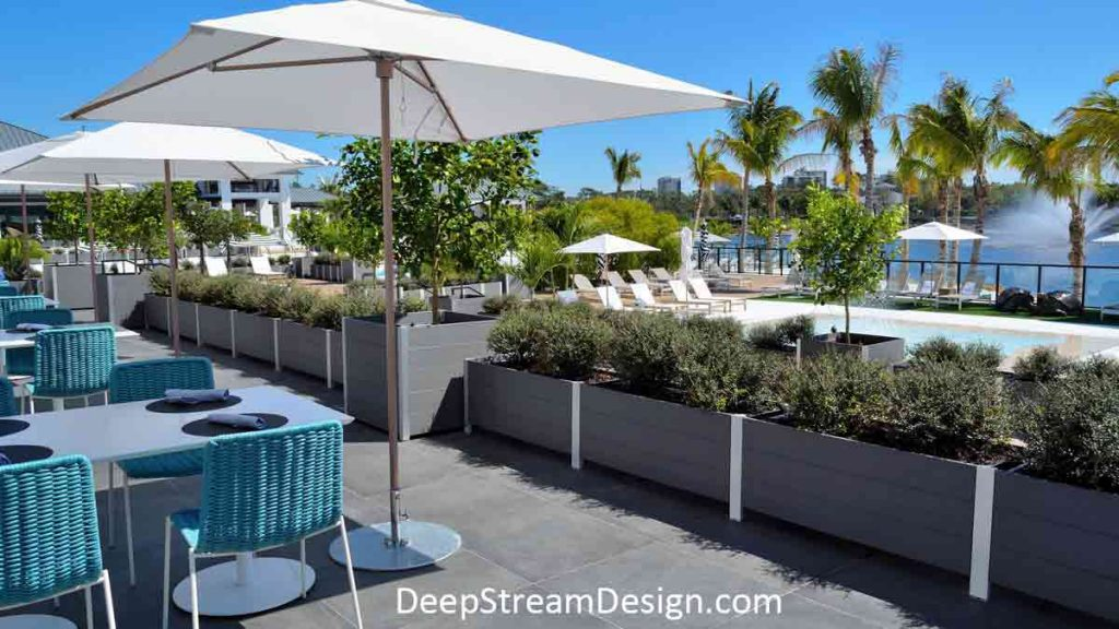 Large Restaurant Planters in slate grey recycled plastic lumber and aluminum, landscaped with trees and bushes, separate the outdoor seating section of a clubhouse restaurant under white umbrellas from the sparkling blue pool.
