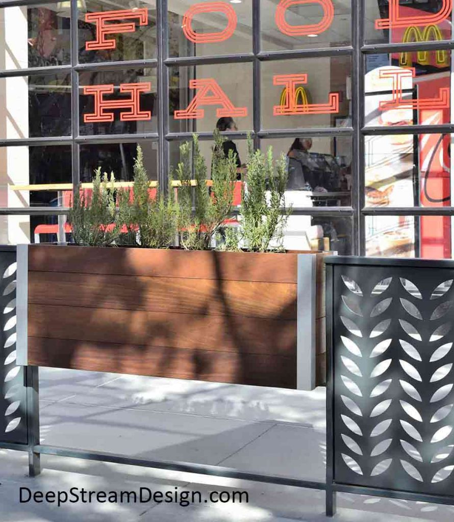 A railing mounted wood planter creates a natural atmosphere for a sidewalk dining area in front of an urban fast-food hall.