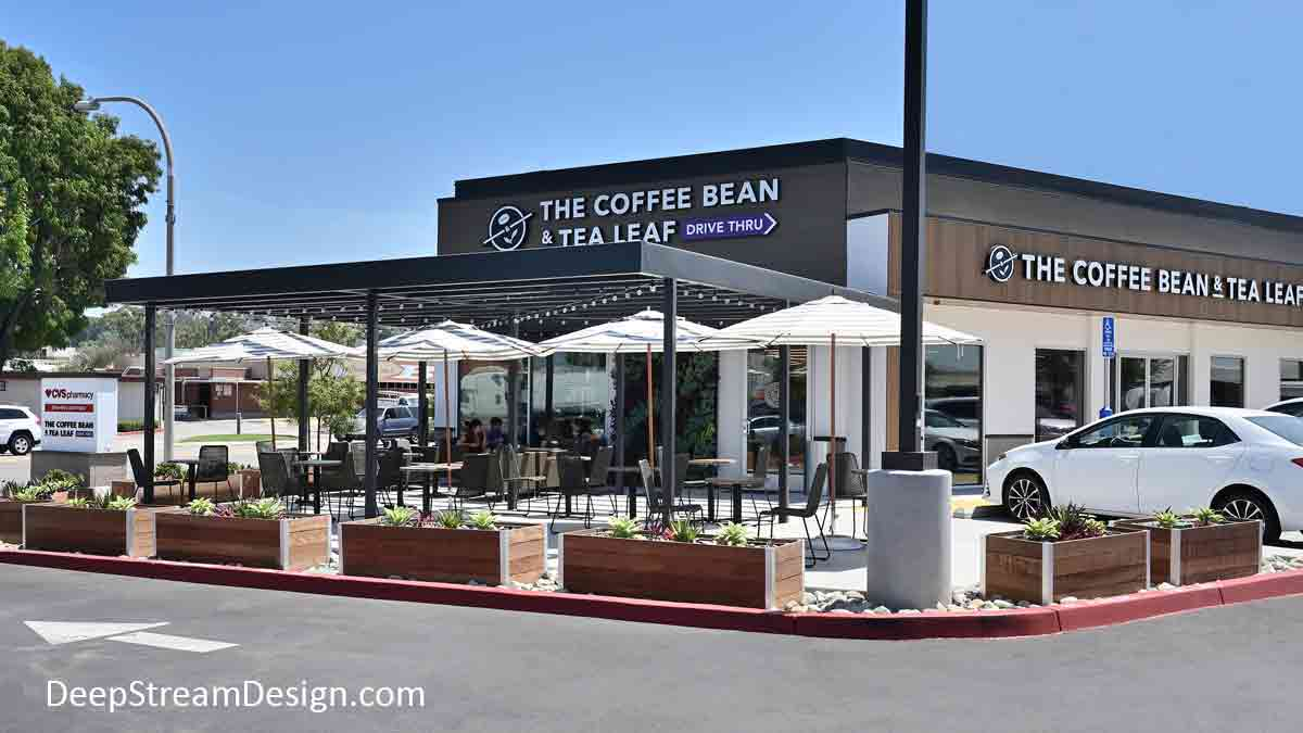 A shopping center stand-alone Coffee Bean coffee shop with outdoor seating under shade surrounded by 10 DeepStream tropical hardwood Restaurant Cafe Planters.