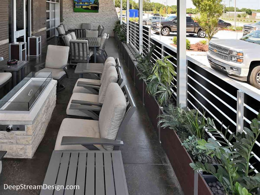 The interior view of a mid-scale restaurant's outdoor smoking section on the sidewalk adjacent to the parking lot created using bronze maintenance free recycled plastic lumber Restaurant Planters with integrated anodized aluminum screen wall.