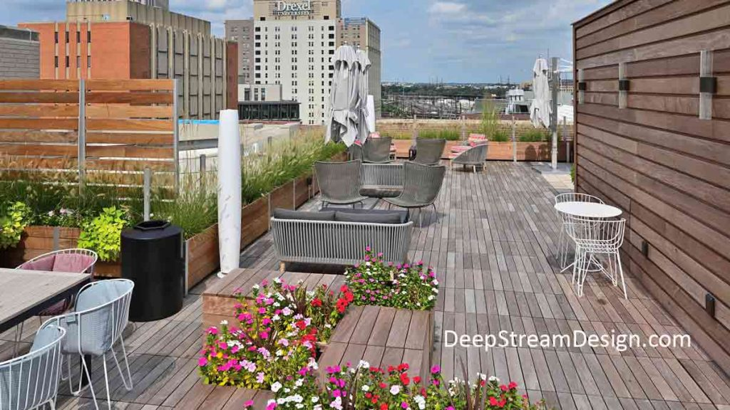 Multi-Section Restaurant Planters, landscaped with ornamental grass and mounted with wood and glass screen wall, create a parapet wall for a roof deck dining area with a dramatic city skyline as a backdrop.