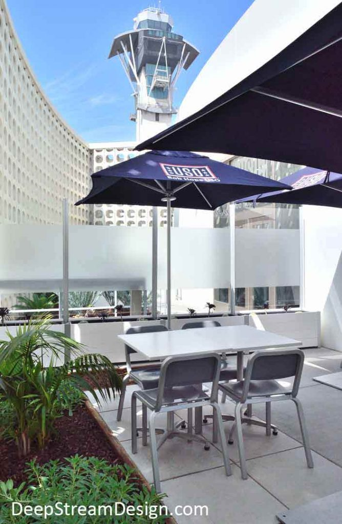 White Restaurant Planters with integrated glass security screen wall with the spectacular modern architecture of the Los Angeles International Airport central hub and control tower as a backdrop.