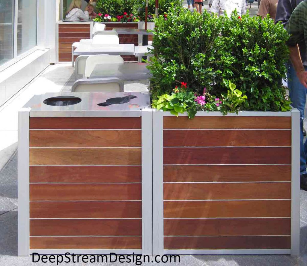 Brightly landscaped Wood Restaurant Planters filled with flowers and companion Audubon Modern Combination Recycling and Trash Receptacles create an outdoor seating area on a busy urban sidewalk.