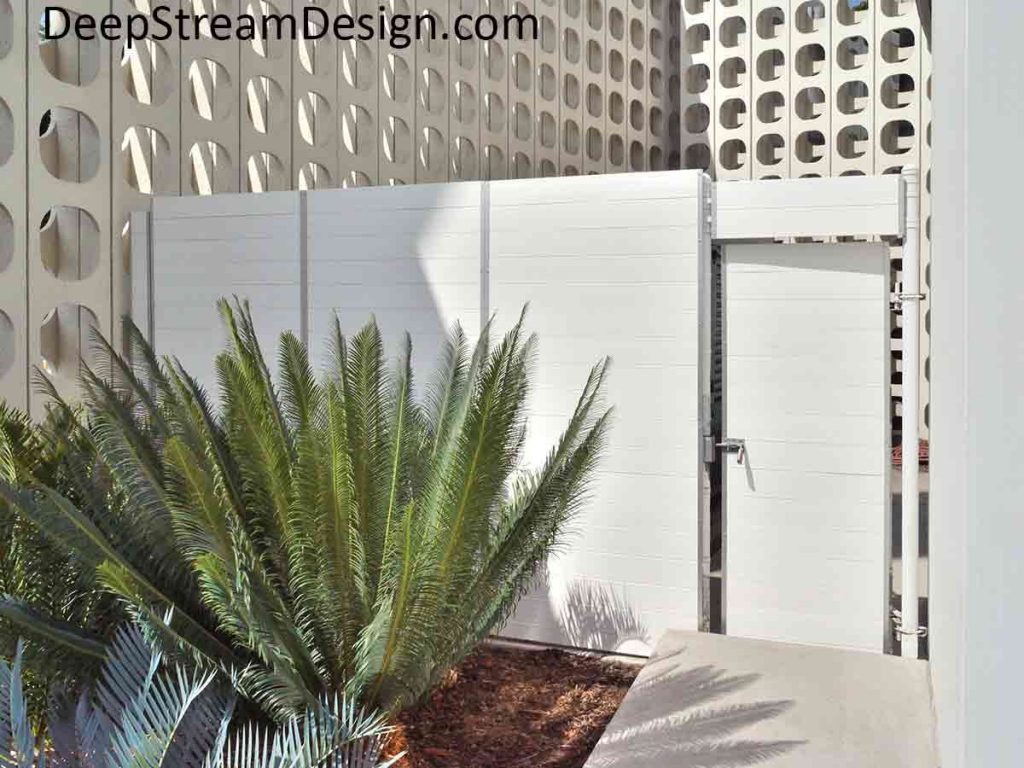 White Screen Wall fencing hides restaurant trash bins and other spaces as seen here with a cycad palm in front as landscaping.
