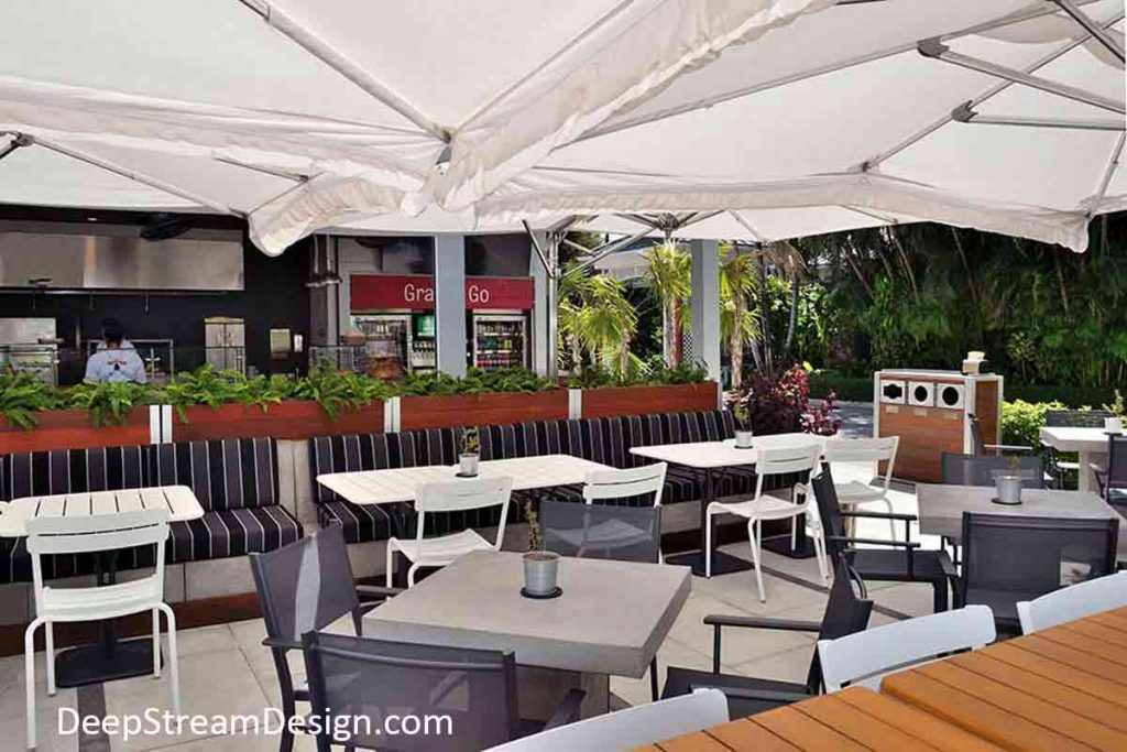 A casual upscale restaurant on a tropical island is created with a tall movable wood restaurant planter wall on wheels allowing the open kitchen to be highlighted while directing traffic to create a calm outdoor dining space under overlapping white umbrellas.