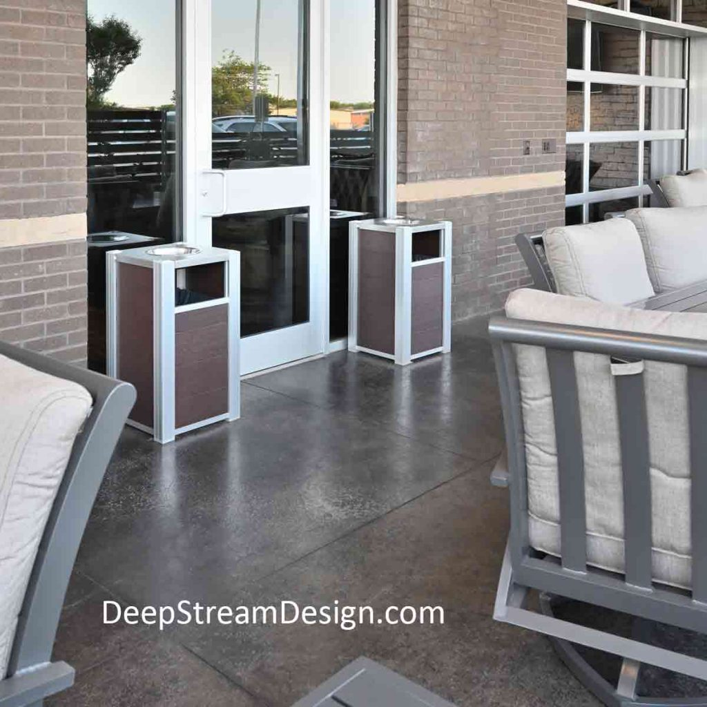 Two Modern Commercial Restaurant Trash Receptacles with ashtray tops flank the outside door leading from an open air smoking section into the restaurant.