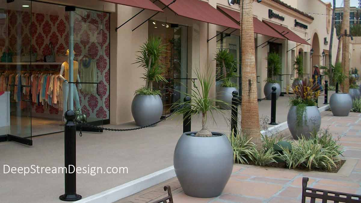 The traditional water-jar shape inspired range of Aquarian Collection of Fiberglass Garden Planters and Pots with a contemporary polished gray finish line a shopping plaza with a modern Mediterranean feel.