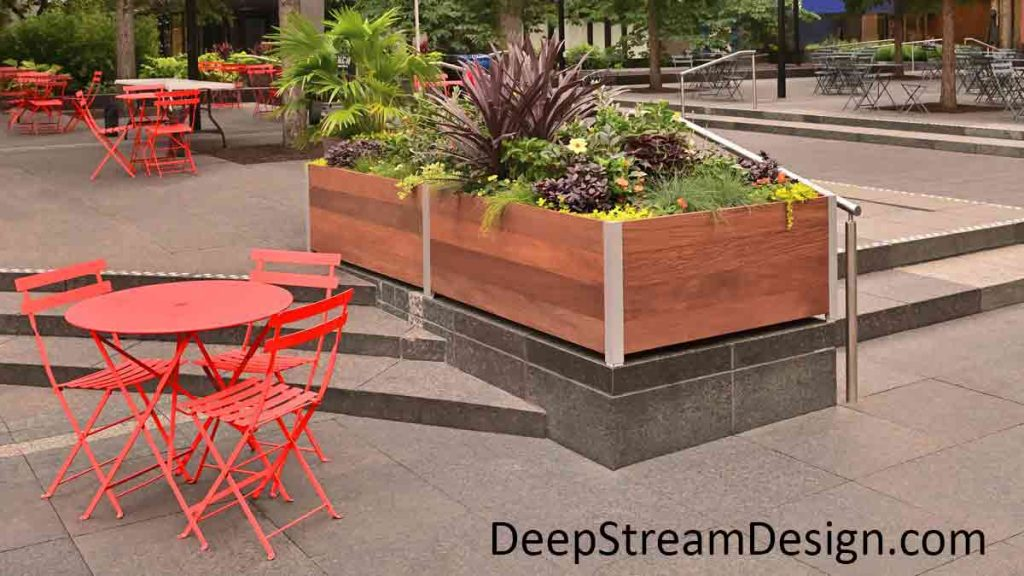 Long Rectangular Commercial Wood Planters overflowing with flowering plants separate dining spaces, with bright orange chairs and tables, on a granite city center plaza while also acting as protective parapet walls around steps between levels.
