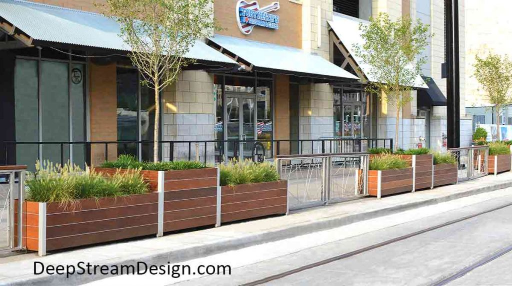A series of long modern square and rectangular Commercial Wood Planters of varying heights, planted with trees and ornamental grass, line an urban sidewalk, acting as a safety barrier between the sidewalk and autos on the street.