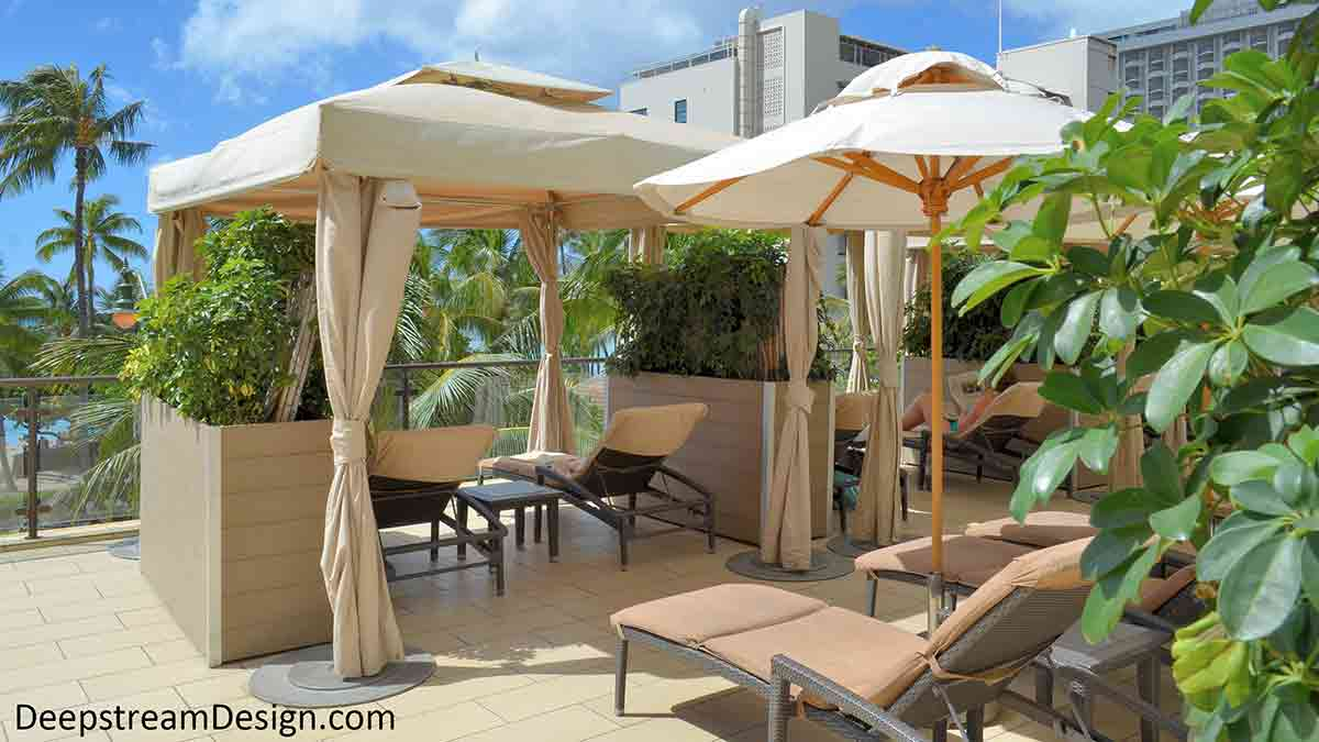 Tall movable Food Safe Plastic Planters on Wheels, crafted of weather wood colored maintenance free recycled plastic lumber, create privacy by separating lounge areas on a pool deck of a Hawaiian hotel overlooking the Pacific Ocean.