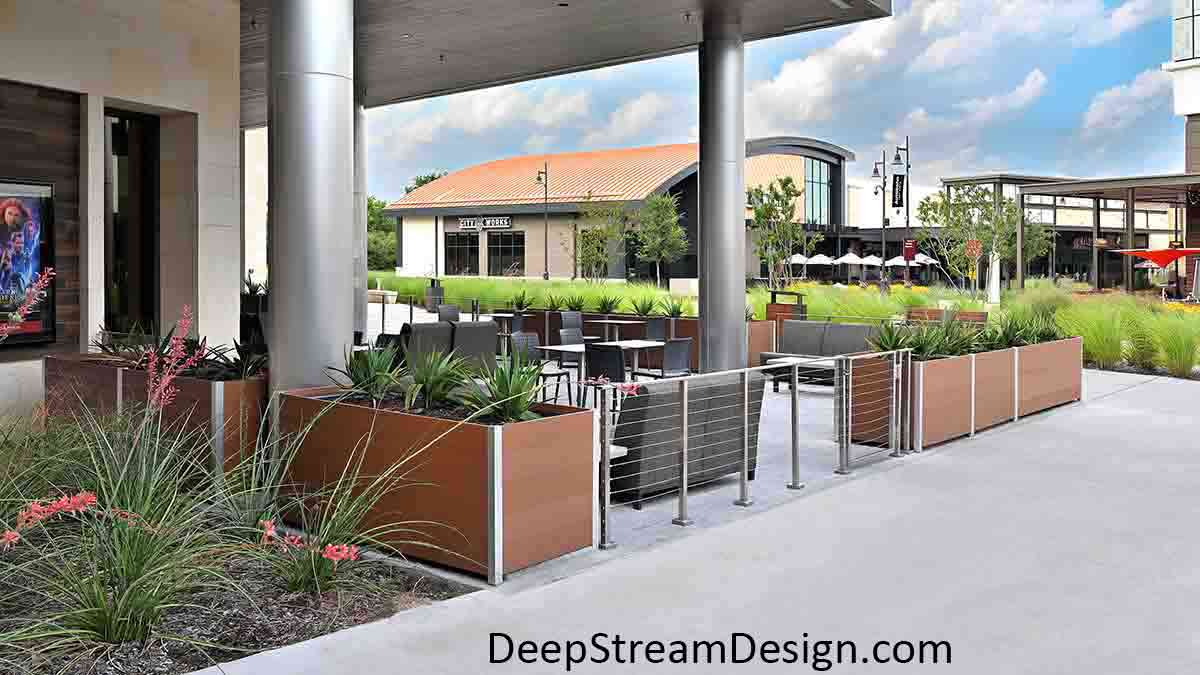 Rectangular, Long Wood Garden Planters crafted with no-maintenance tropical hardwood colored recycled plastic lumber create an outdoor seating area in front of a movie theater at a modern outdoor suburban mall.