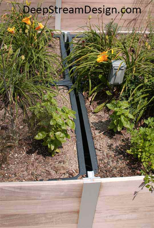 A close-up picture showing how a Commercial Wood Planter's hidden frame supports a waterproof planter liner filled with flowers.