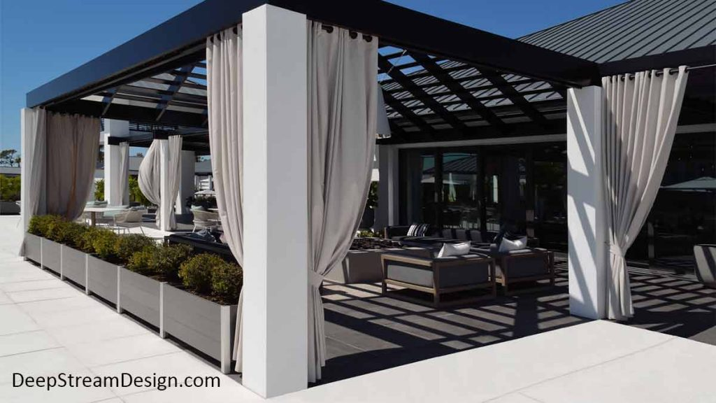 Chic modern Long Wood Garden Planters in slate grey no-maintenance recycled plastic lumber and anodized aluminum control access to a modern clubhouse outdoor lounge with long white curtains pulled back around a ceiling shade grid open to the bright blue sky.