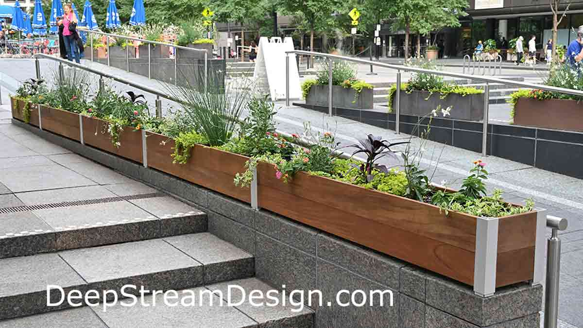 A busy urban central plaza uses lushly landscaped shallow, narrow, Long Wood Garden Planters as a parapet wall topping the granite divider between steps and a ramp up to a fountain to keep skateboarders from damaging them.