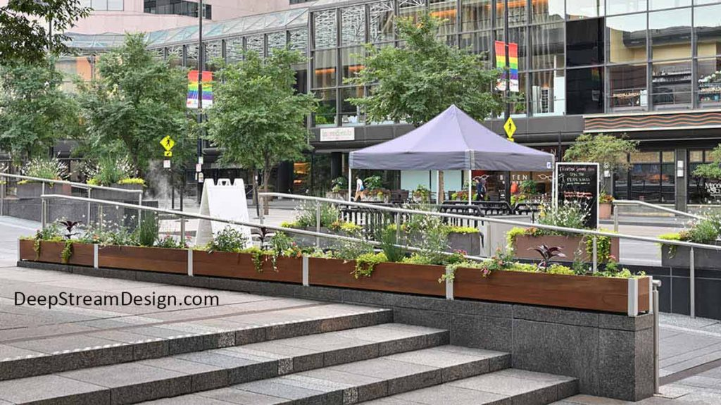 A busy urban central plaza uses lushly landscaped shallow, narrow, rectangular, Commercial Wood Planters as a parapet wall, topping the granite divider between steps and a ramp up to a fountain to keep skateboarders from damaging them.