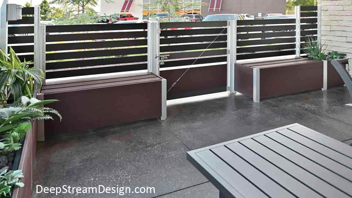 Modern Ipe Brown Storage Box Benches flank a planter mounted gate set in a series of Mariner recycled plastic Long Wood Garden Planters used to anchor aluminum screen wall that defines the outdoor seating area of a restaurant.