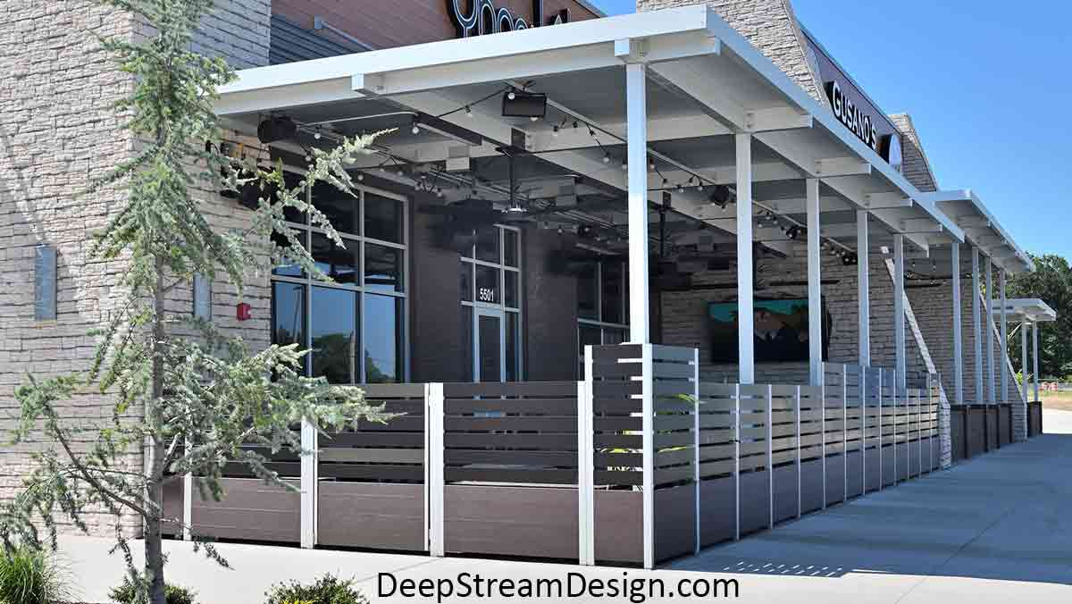 The exterior view of a large Ipe Brown modular commercial Long Wood Garden Planter and aluminum screen wall installation, complete with gates, bench seats, and landscaping, that encloses a restaurant's outdoor smoking area.