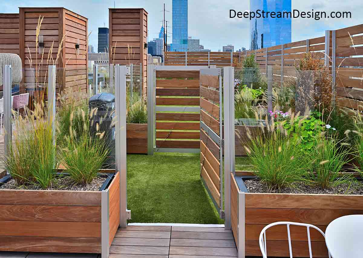 A double planter gate capture compound for animal control for a roof terrace dog park, created using modern landscaped modular commercial Long Wood Garden Planters anchoring glass and wood screen walls with a high-rise central business district in the immediate background.