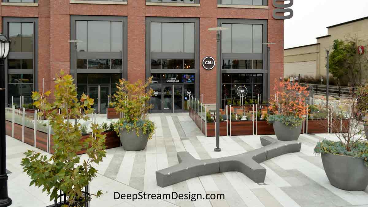 Landscaped modern Ipe Long Wood Garden Planters anchor glass screen walls and lights enclosing an outdoor plaza seating area in front of an upscale wine bar restaurant in a modern glass and brick building.
