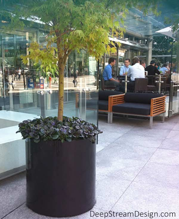 A round dark bronze painted aluminum planter holds a tree for accent in a bright glass and marble atrium and entrance lobby of a commercial building.