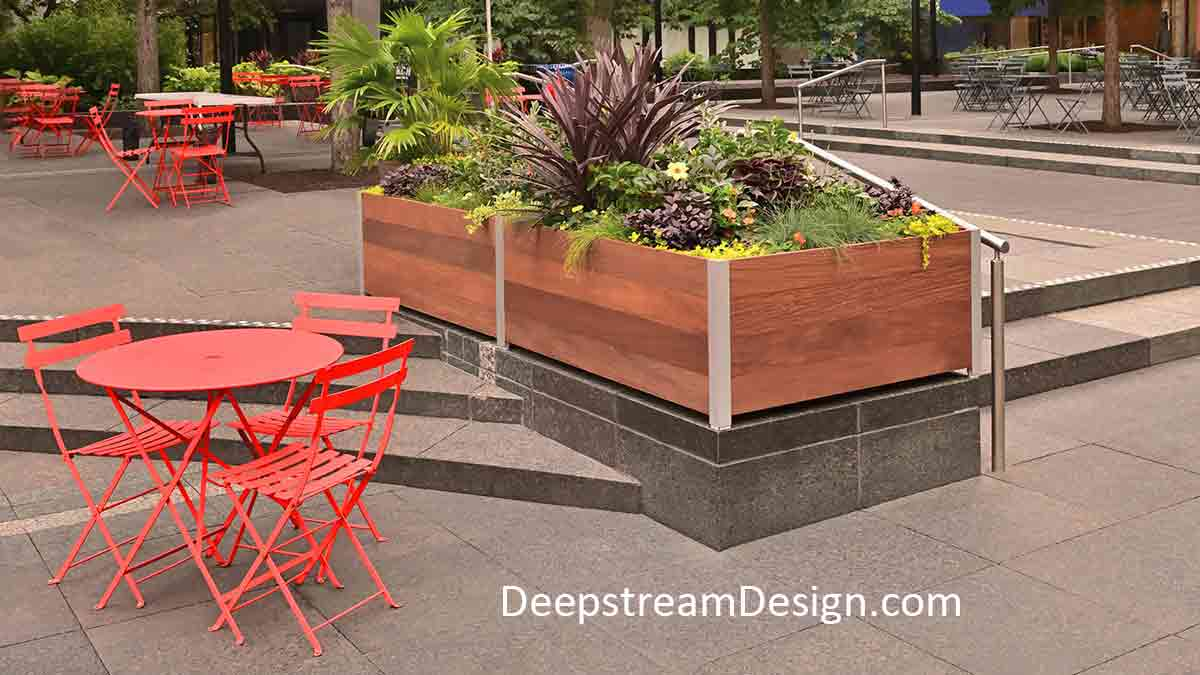 Long Wood Garden Planters overflowing with flowering plants separate dining spaces, with bright orange chairs and tables, on a granite city center plaza, while also acting as protective parapet walls around steps between levels.