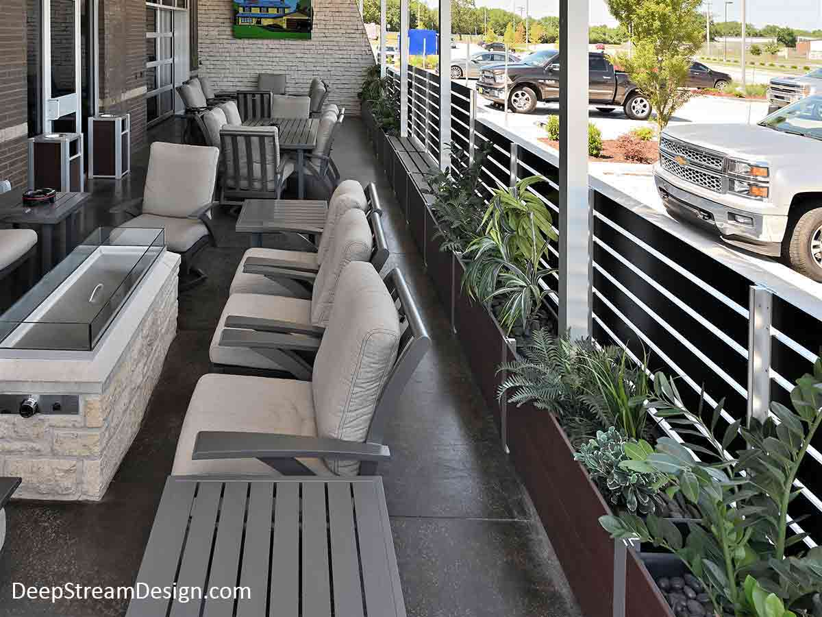 The interior view of a large Ipe Brown modular commercial Long Wood Garden Planter and aluminum screen wall installation, complete with planter mounted gates, bench seats, matching ash-trash receptacles, and landscaping, enclosing a restaurant's outdoor smoking area.