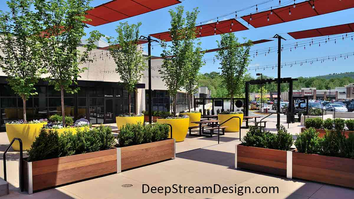 Several modern Commercial Long Wood Garden Planters with bushes divide up a plaza area of an outdoor mall's food court seating area and provide a safety barrier between levels.