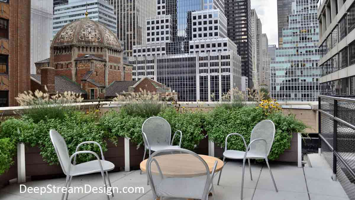 A lushly landscaped, Long Wood Garden Planter softens a parapet wall to create an intimate dining area on a midtown Manhattan roof deck with NYC skyscrapers as dramatic urban backdrop.