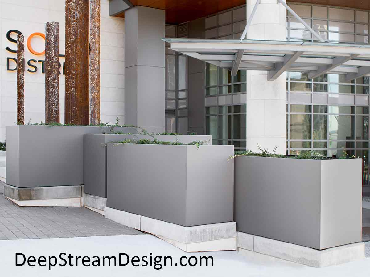 A complex arrangement of large, tall, grey powder coated aluminum planters on stepped concrete bases enhance the dramatic entrance of a modern building with equally complex windows and offset glass and aluminum overhang, juxtaposed with a steel columnar art installation.