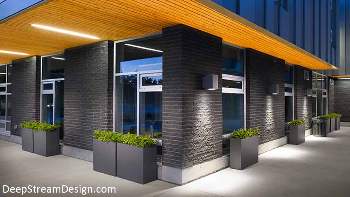 Modern tall rectangular aluminum planters with slate grey powder coating accent clean crisp modern architecture and windows of a modern gray brick building with natural wood clad overhangs and dramatic downlighting at night.